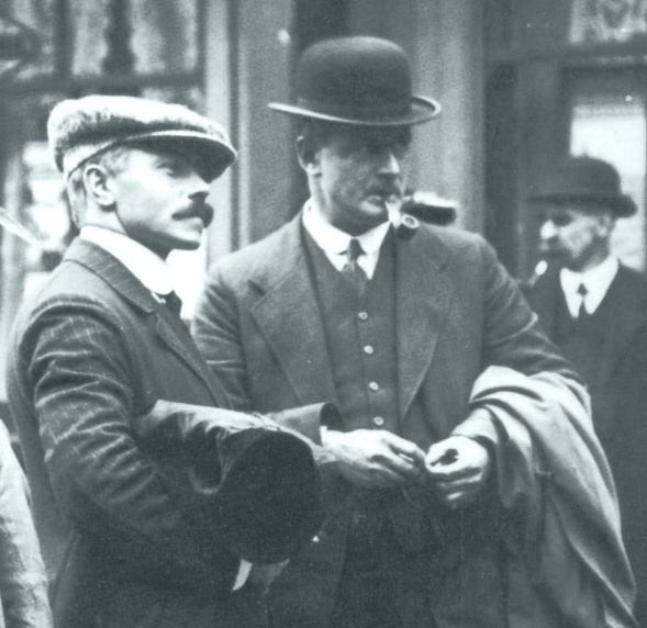 Lightoller (au centre, chapeau melon et pipe), et Pitman (à gauche, moustache et casquette) en tenue de ville dans une rue.
